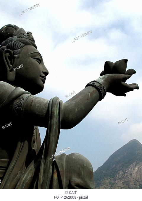 A statue offering a lotus flower to the Big Buddha, Lantau Island, Hong Kong