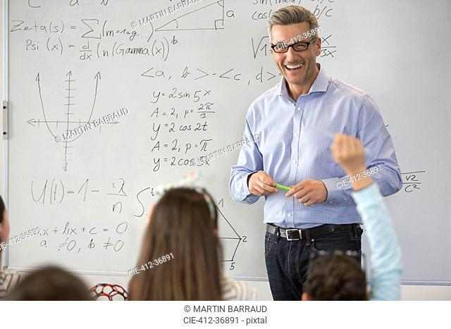 Smiling male science teacher leading lesson at whiteboard in classroom
