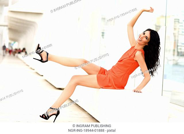 Brunette woman, model of fashion, wearing orange short dress moving her long legs. Young girl with curly hairstyle happy in an urban street