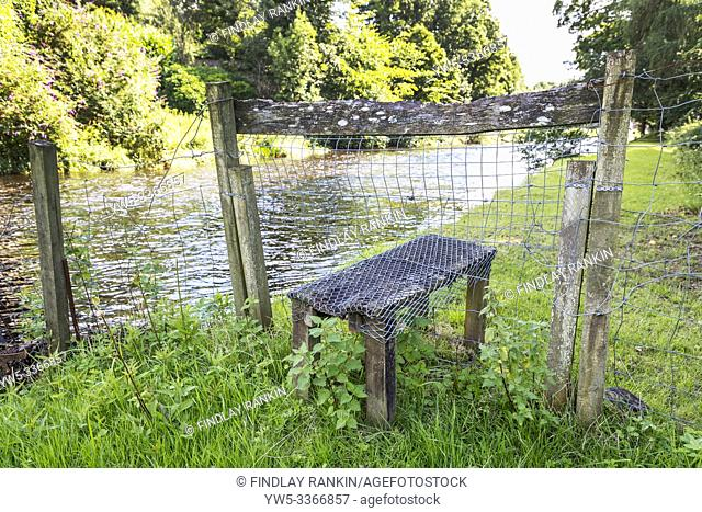 old wooden stile across a wooden fence giving access to a public walk along the side of the River Doon, near Ayr, Ayrshire, Scotland, UK