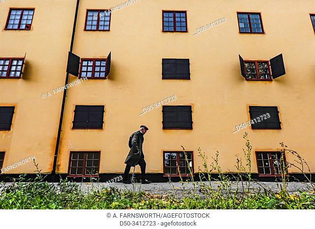 Stockholm, Sweden A senior man walks by a classic orange building on the island of Skeppsholmen