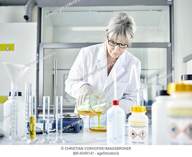 Female analytical chemist, gray hair, 50-55 years, filling a chemical mixture of water and Potassium ferrocyanide into a glass container, Wattens