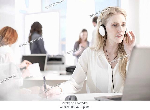 Portrait of woman at desk in office wearing headphones
