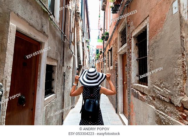 Rear View Of Women Walking Through A Narrow Alley In The City Center Of Venice