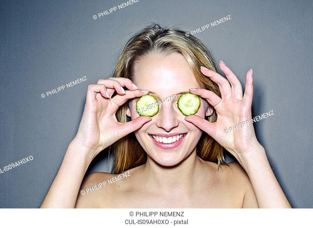 Young woman with cucumber slices covering eyes