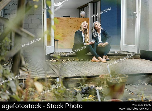 Mature and young businesswoman sitting on terrace