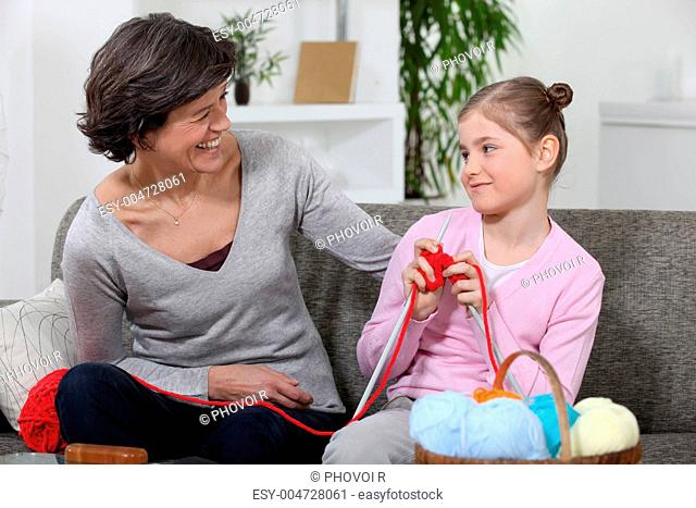 Woman teaching her granddaughter how to knit