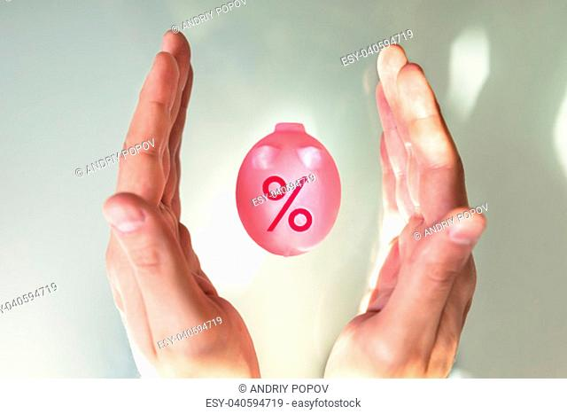 High Angle View Of A Person's Hand Protecting Piggybank With Percentage Symbol On Desk