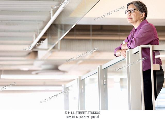 Filipino businesswoman standing at office balcony