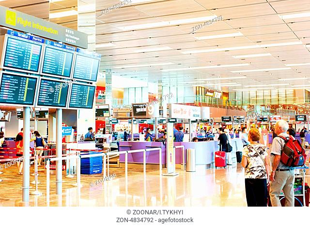Singapore, Republic of Singapore - March 05, 2013: People looking at depature arrival board at Changi International Airport