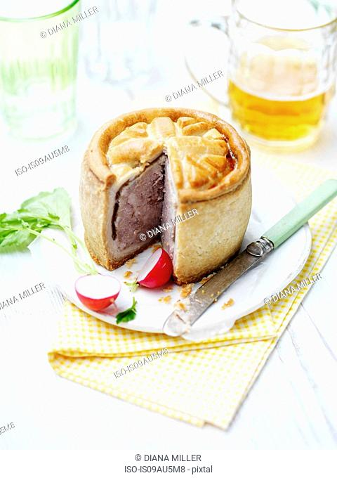 Union jack topped pork pie with radishes and beer on vintage table cloth