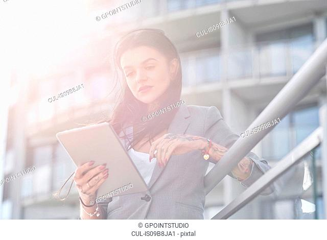 Businesswoman outdoors, using digital tablet, tattoos on hands