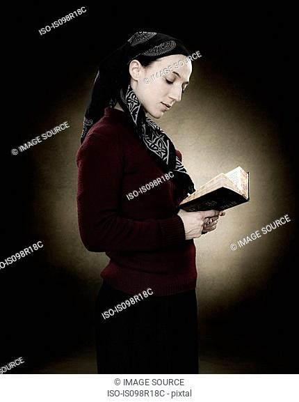 A young jewish woman reading a prayer book