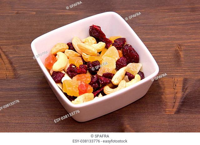 Dried fruits on a square bowl on wooden table