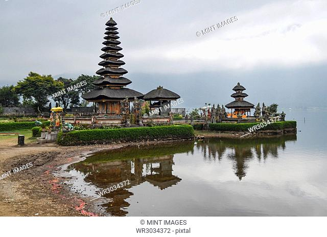 Balinese Hindu Temple, Ulu Danu Beratan, traditional architecture and tall towers with tiered tapering roofs in a valley on the shores of Lake Bratan