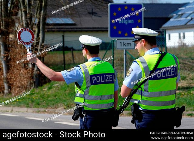 09 April 2020, North Rhine-Westphalia, Mützenich: Federal police officers check a car coming from Belgium at the border to Belgium near Monschau in the Eifel