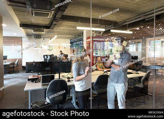 start up business planning and making organization with young couple at modern office interior writing notes on stickers