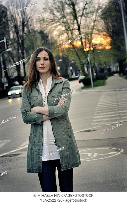 Portrait of a young woman on city street