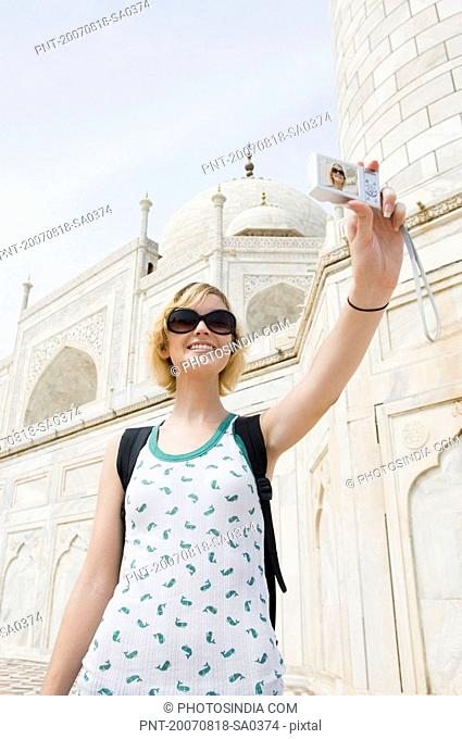Low angle view of a young woman taking a picture of herself, Taj Mahal, Agra, Uttar Pradesh, India