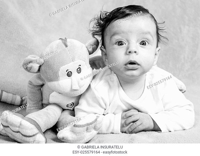 Portrait of an adorable smiling baby playing with a monkey toy