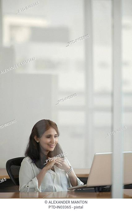 Singapore, Businesswoman using laptop in office