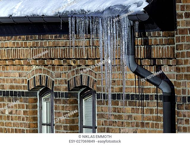 ice needles with Water Spout with brick walled building