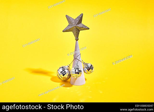 Christmas tree as concrete conus with golden star and disco balls. 90s new year party . High quality photo