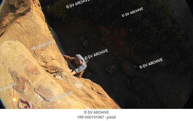 Aerial-shot of a rock climber climbing up a cliff face