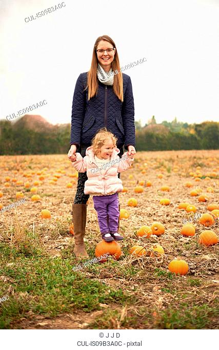 Portrait of mid adult woman and toddler daughter standing on top of pumpkin in field