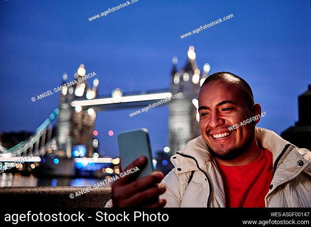 Smiling man taking selfie on mobile phone in front of Tower Bridge at night