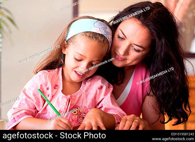 Concentrated mother helping her daughter for homework