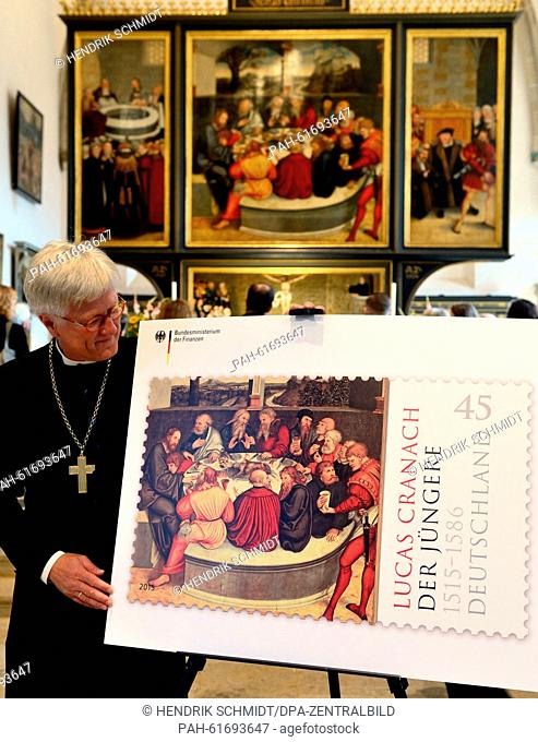 The chairman of the Council of the Evangelical Church in Germany, Heinrich Bedford-Strohm, stands in front of the Cranach altar presenting a commemorative stamp...