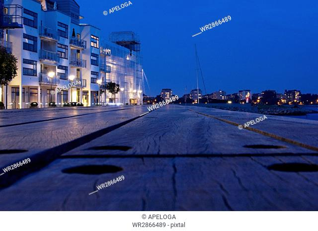 Surface level of street outside buildings against clear blue sky at dusk