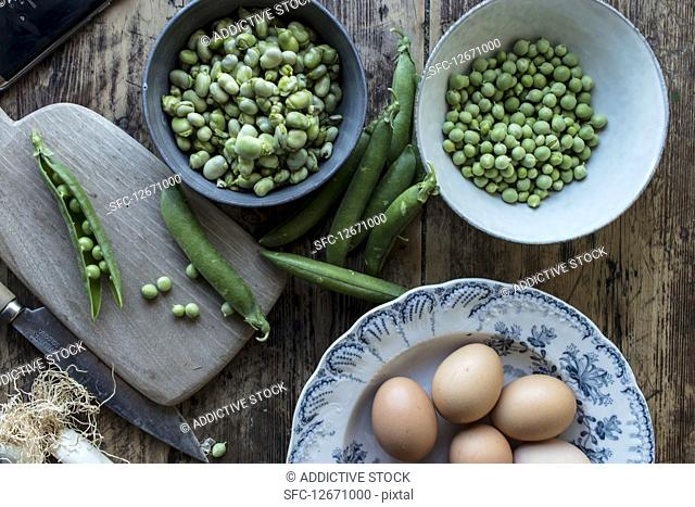 From above of rope fresh green peas in bowl and eggs on wooden table while cooking
