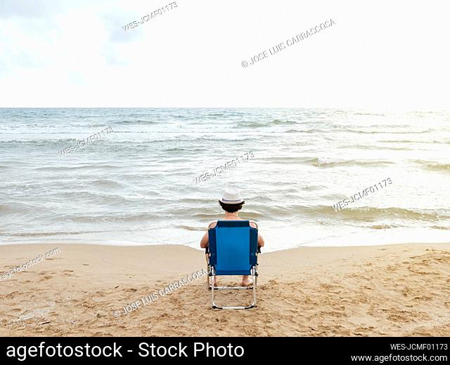 Rear view of man sitting in beach lounger on the beach