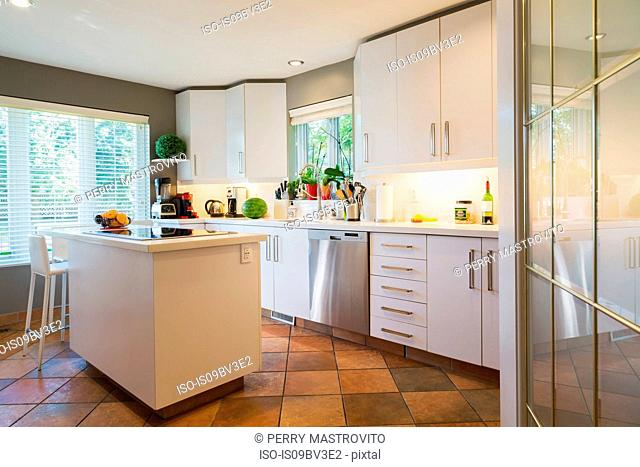 White cabinets, quartz countertop and island with glass hob and high back barstool in kitchen