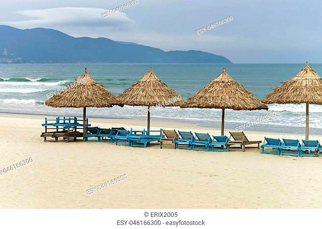 Palm shelters and sunbeds in the China Beach in Da Nang, in Vietnam. It is also called Non Nuoc Beach. South China Sea and Marble Mountains on the background
