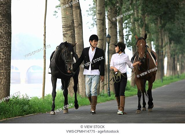 Young couple holding horse walking side by side