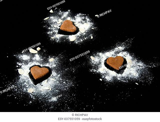 Three gingerbread hearts with almond and flour isolated on black background