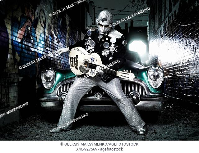 Silver Elvis with a guitar and a retro car in a graffiti painted street  Performing artist Peter Jarvis from Toronto Canada