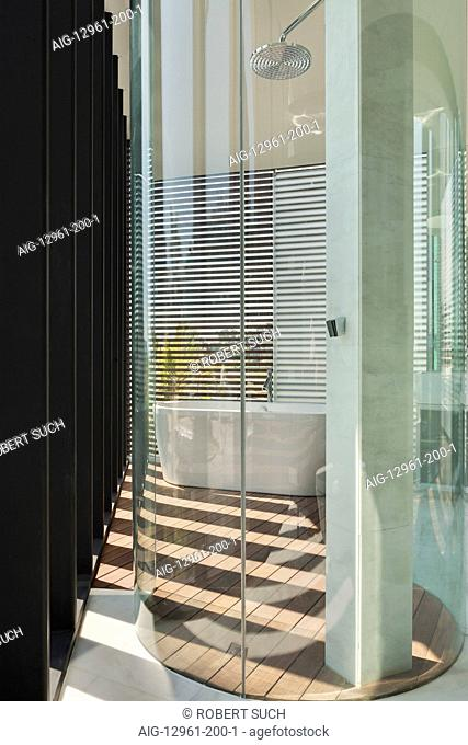 Glass drum shower cubicle in modern bathroom with venetian blinds and patterns of light