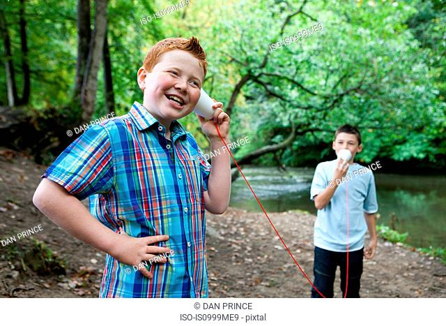 Two boys using paper cups and string to communicate in woodland