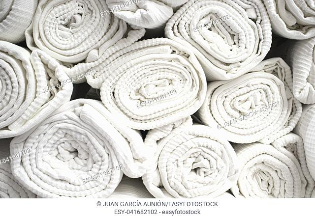 Loads of rolled white cotton bedspreads. Closeup