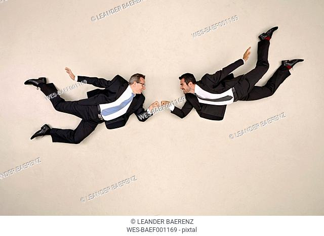 Two flying businessmen doing fist bump