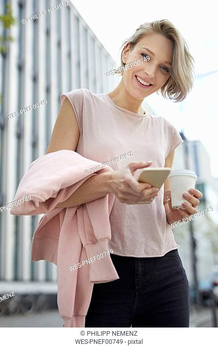 Portrait of happy blond woman with takeaway coffee and cell phone in the city