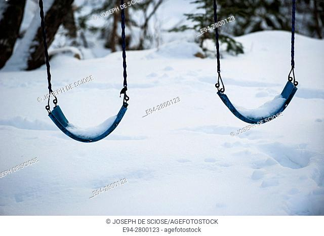 2 seats from a swing set covered in snow and snow on the ground, Nova Scotia, Canada