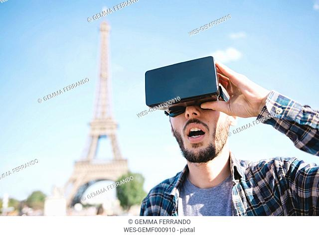 France, Paris, man traveling to Paris via virtual reality glasses