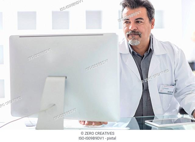 Male doctor working at computer
