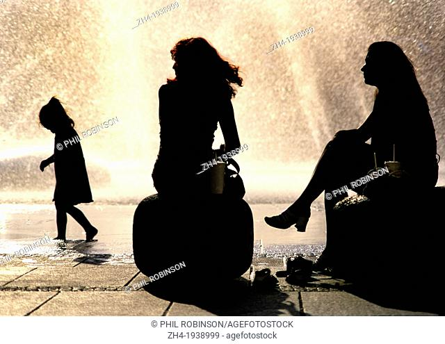Munich, Bavaria, Germany. Two women and a child in silhouette by the fountain in Karlsplatz (square)