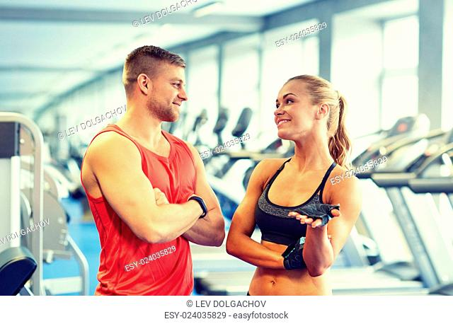 sport, fitness, lifestyle and people concept - smiling man and woman talking in gym